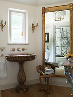 In the bathroom, a marble pedestal washbasin and a gilt-framed mirror give the room a Classical feel.