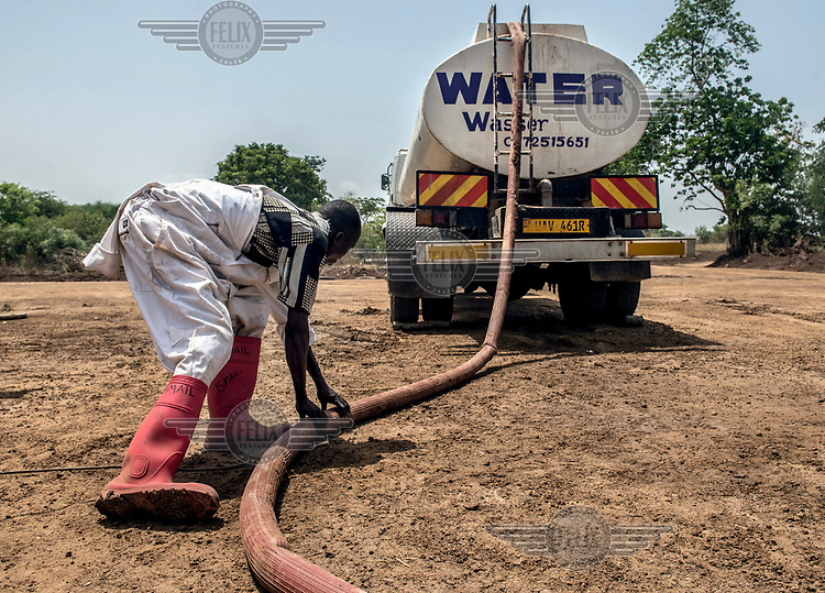 A Red Cross worker fills a truck with water at a treatment plant beside the river Nile.