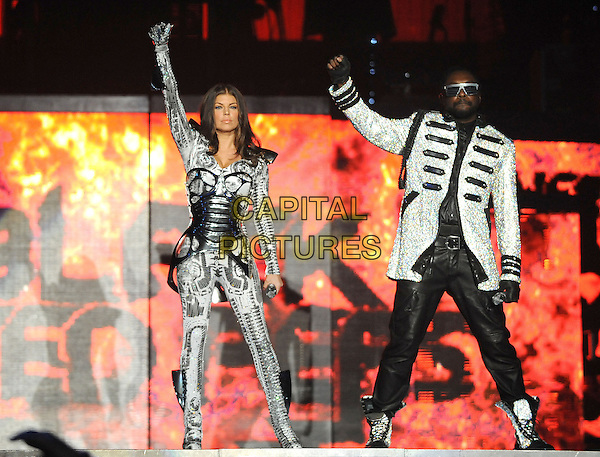 "WILL.I.AM & FERGIE - BLACK EYED PEAS.(Stacy Ferguson, William James Adams, Jr.) .performs live at Staples Center as part of their ""The E.N.D. Tour"" in Los Angeles, California, USA, March 29th, 2010..music band live on stage concert gig.full length space age silver suit costume catsuit glove arm microphone side sunglasses fingerless gloves jacket military leather trousers glasses white metallic hand arm raised up    boots lace-up trainers sparkly glittery glitter                                           .CAP/RKE/DVS.©DVS/RockinExposures/Capital Pictures."