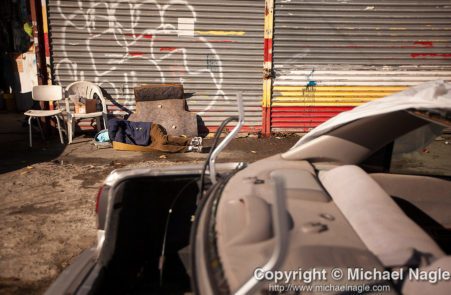 QUEENS, NY -- NOVEMBER 18, 2013:  A customer sleeps on the ground, work is performed on his car,  on November 18, 2013 in Queens.  PHOTOGRAPH BY MICHAEL NAGLE FOR THE NEW YORK TIMES