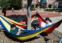 NWA Democrat-Gazette/CHARLIE KAIJO Luis Duran of Springdale and Elisabeth Sugg of Springdale (from left) relax on hammocks between their classes, Monday, October 8, 2018 at the Northwest Arkansas Community College in Rogers.