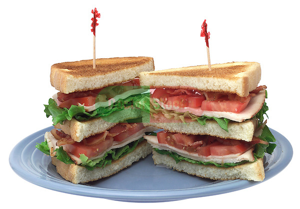 sandwich plate with triple decker turkey club, lettuce tomatoes, bacon, white bread on shadowless white background