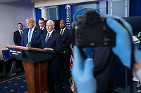 A photographer wears protective gloves as United States Vice President Mike Pence, joined by United States President Donald J. Trump and members of the Coronavirus Task Force, makes remarks on the Coronavirus crisis in the Brady Press Briefing Room of the White House in Washington, DC on Saturday, March 21, 2020.  Credit: Stefani Reynolds / Pool via CNP/AdMedia