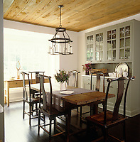 An antique farm table in the kitchen is complimented by a set of antique Chinese chairs