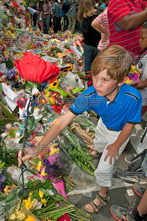 A boy places a flower on a pile of bouquets left outside Nelson Mandela's house in Houghton, Johannesburg, two days after the former South African President died on 5 December 2013.