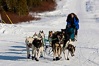 Cindy Gallea runs down the road as she arrives at the Elim checkpoint during the 2010 Iditarod