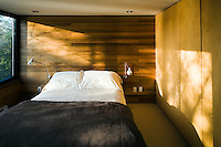 The walls of the simple wood-lined bedroom glow in the light of the evening sun reflected off the lake