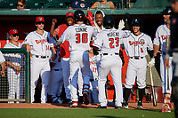 Lansing Lugnuts Griffin Conine (38) high fives teammates after hitting a two run home run that also scored Gabriel Moreno (23) during a Midwest League game against the Burlington Bees on July 18, 2019 at Cooley Law School Stadium in Lansing, Michigan.  Also shown is Rafael Lantigua (9), DJ Neal (towel over head), Reggie Pruitt (red top), and Troy Miller (14).  Lansing defeated Burlington 5-4.  (Mike Janes/Four Seam Images)