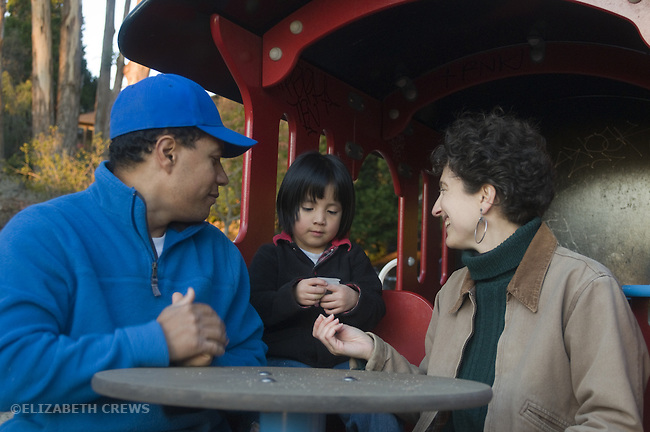 Berkeley CA Adoptive parents playing fantasy train conductor game with Gualemalan daughter, three and a half, in park play train  MR