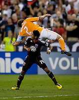 Andy Najar (14) of DC United goes underneath Eddie Robinson (2) of the Houston Dynamo and commits the foul during their game at RFK Stadium in Washington, DC.  Houston defeated D.C. United, 3-1.