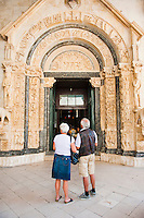 Tourists visiting the Cathedral of St Lawrence, Trogir, Dalmatian Coast, Croatia, Europe. This photo shows a couple of tourists visiting the Cathedral of St Lawrence, the most famous cathedral in Torgir. Trogir is a beautiful old town on the Dalmatian Coast of Croatia and is on the UNESCO World Heritage List thanks to it's stunning Romanesque Cathedral's and architecture.