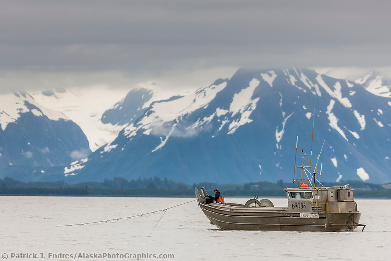 Chugach mountains in the distance of a bow picker boat during a commercial drift gill net opener on the Copper River Delta near Cordova, Alaska.