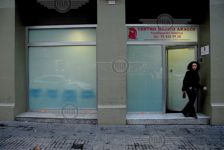 A woman exits the health clinic Centro Medico Aragon in Barcelona.
