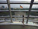 A visitor walking in the Norman Foster-designed glass cupola on the roof of the Reichstag, the German Parliament building in the city centre adjacent to where the Berlin Wall ran. The Wall divided Berlin and Germany for 29 years from 1961. A popular uprising took place in East Germany in 1989 and lead to the end of the Cold War and the re-unification of Germany after which Berlin became the nation's capital city once more.