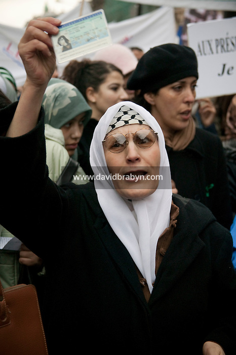 An elderly woman wearing an Islamic head scarf holds up her French ID card as she takes part in a street protest in Paris; France, 17 January 2004, against a law that plans to restrict the wearing of veils in public schools.