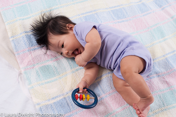3 month old baby girl Asian Chinese American grasping toy with one hand and rolling onto side horizontal