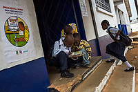 MONROVIA, LIBERIA - FEBRUARY 16: Students read a book as they attend the first day of school since schools closed due to the Ebola outbreak 6 months ago, at the C.D.B. King Elementary School on February 16, 2015 in Monrovia, Liberia. Though Ebola cases have receded into the single digits in Liberia, lingering fear and a depressed economy have dampened the turnout at schools. Many have yet to reopen, having failed to meet the minimum requirements put in place to prevent the transmission of the virus. Many of those that have reopened &ndash; like C.D.B. King, which, though located in the center of the capital, lacks electricity and running water, and has only a few toilet stalls for a student population that numbered 1,000 before Ebola &mdash; are struggling.<br /> Daniel Berehulak for The New York Times