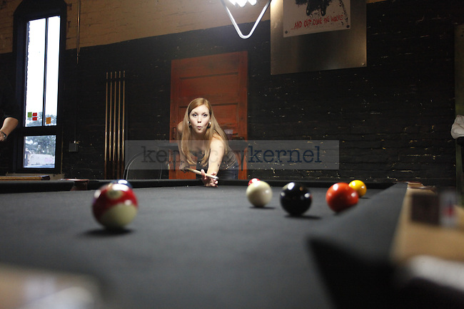 Danielle Goulding, UK alumna, takes a shot at the pool table on September 4 during the grand reopening of Buster's on Manchester Street. Photo by Zach Brake | Staff