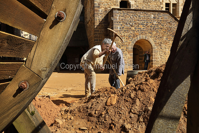 Men breaking rubble with pick axes on the building site in the courtyard at the Chateau de Guedelon, a castle built since 1997 using only medieval materials and processes, photographed in 2017, in Treigny, Yonne, Burgundy, France. The Guedelon project was begun in 1997 by Michel Guyot, owner of the nearby Chateau de Saint-Fargeau, with architect Jacques Moulin. It is an educational and scientific project with the aim of understanding medieval building techniques and the chateau should be completed in the 2020s. Picture by Manuel Cohen