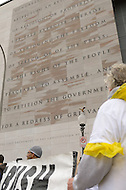 November 23, 2011  (Washington, DC)   Participants in the OccupyDC movement stop and read aloud the First Amendment etched on the facade of the Newseum in Washington.  The group marched to the U.S. Capitol.  (Photo by Don Baxter/Media Images International)