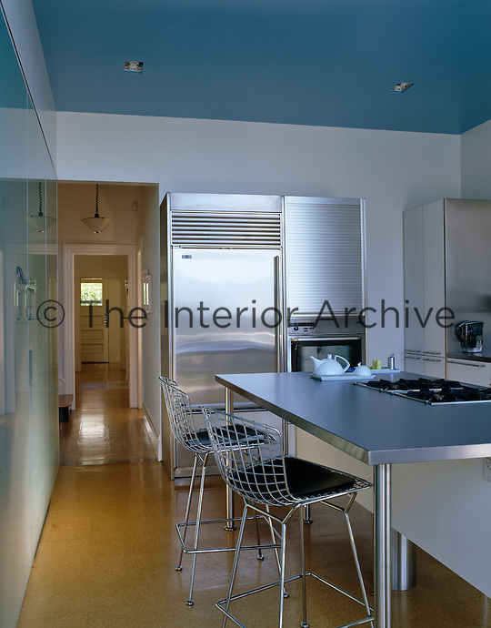 A contemporary kitchen with a pair of bar stools and a stainless steel island that houses the hob