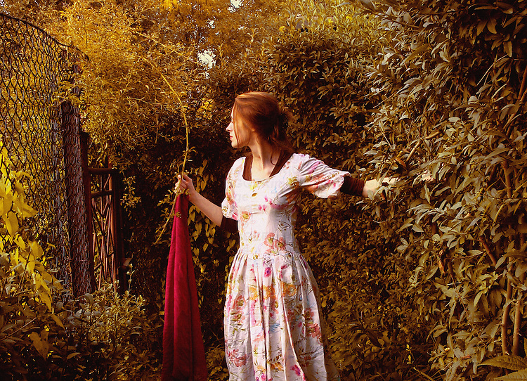 A woman in a white dress, standing in a garden and holding a long red scarf.