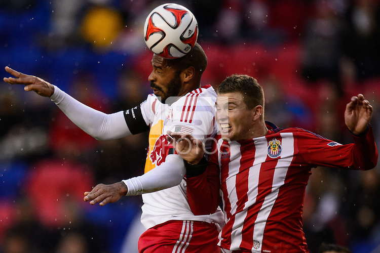 Thierry Henry (14) of the New York Red Bulls goes up for a header with Eriq Zavaleta (22) of Chivas USA. The New York Red Bulls and Chivas USA played to a 1-1 tie during a Major League Soccer (MLS) match at Red Bull Arena in Harrison, NJ, on March 30, 2014.