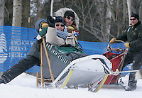 Jon Korta sticks his leg out for counter-balance as he rounds a turn in Anchorage on Saturday March 1st during the ceremonial start day of the 2008 Iidtarod Sled Dog Race. Waving in the basket is his Iditarider Leigh Leveen from Los Angeles.
