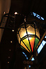 Lantern with multi coloured glass and black metal design.