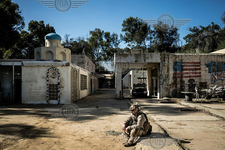 A member of the Navy's bomb detection unit sits on the ground during training to diffuse IEDs (Improvised Explosive Devices) with a remote control bomb diffusion robot called a Packbot, which is over a decade old. The training facility,  located at Spawar (Space and Naval Warfare Systems Command) in San Diego, is meant to resemble a village in the Middle East. Spawar is a research and operations arm of the Navy. The Unmanned Systems Group at Spawar is developing autonomous vehicles for the military, which they think will revolutionise the way the military fights. The challenge is to develop autonomous vehicles sturdy enough to operate in environments where there are no roads.