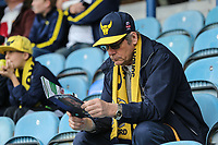 An Oxford United supporter reads the match day programme ahead of the Sky Bet League 1 match between Peterborough and Oxford United at the ABAX Stadium, London Road, Peterborough, England on 30 September 2017. Photo by David Horn.