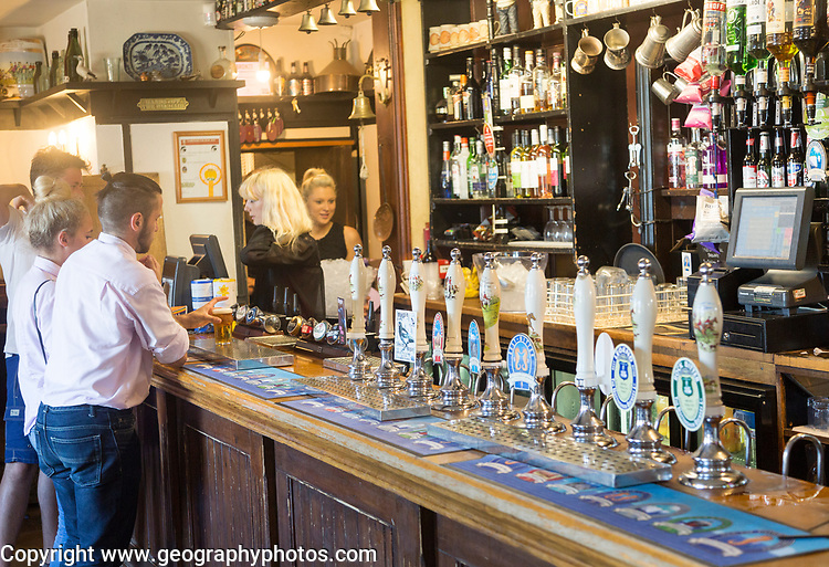 Customers and staff at bar of Bankes Arms Inn public house, Studland, Swanage, Dorset, England, UK