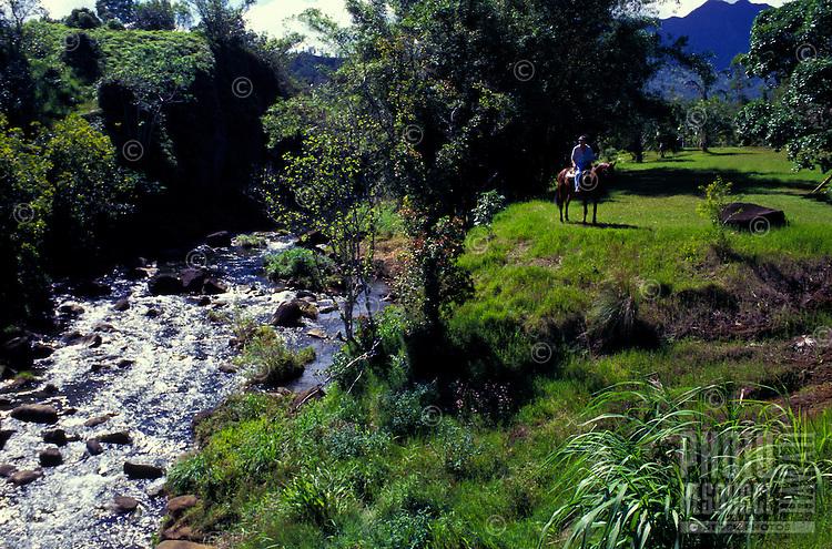 Silver Falls Ranch at Kalihiwai with horseback rider near flowing stream