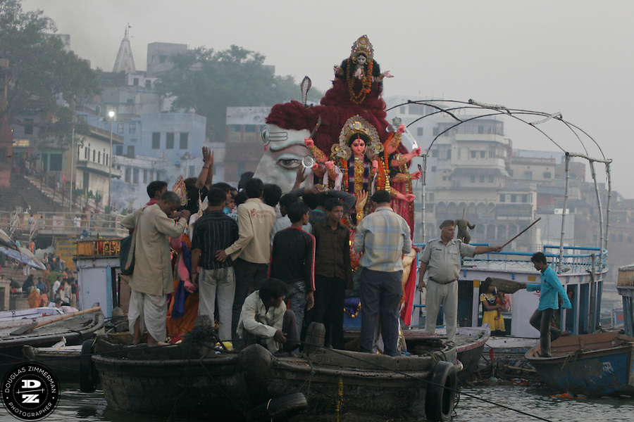 An idol of the Goddess Durga is taken on a boat to be immersed in the Ganges (Ganga) River in Varanasi, India during the festival of Dussehra.  On the tenth day after Navaratri (usually in September or October) is the Hindu  festival of Dussehra / Vijay Dashmi.  The immersion of the Goddess Durga symbolizes  the end of the goddess? brief visit to the earth. Photograph by Douglas ZImmerman
