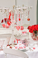 The dining table is decorated for Christmas in a red and white theme