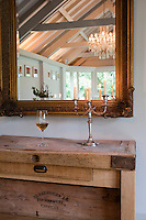 A silver candlestick sits on top of a wooden butcher's block being used as a side table with a gilt framed mirror above. An interior of Whitehouse, a guest house in Chillington, Devon