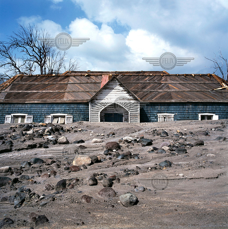 The roof of a destroyed building protrudes from a layer of ash, mud and rock from the pyroclastic flow which descended on the former capital during the Soufriere Hills volcanic eruption. <br /> <br /> The volcano began erupting in July 1995, and remained active through the subsequent decade. Up to 7,000 of the 10,500 inhabitants have been evacuated from the island, while other residents have been moved to the northernmost areas. The southern region affected by the eruption is designated out of bounds to everyone except scientists.