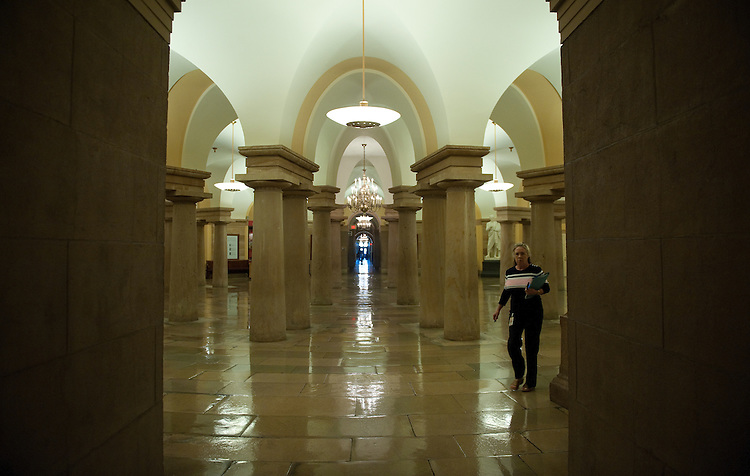 UNITED STATES - August 17: A staffer heads for her office in the The United States Capitol crypt. The crypt is the large circular room filled with forty neoclassical Doric  columns directly beneath the United States Capitol rotunda and was built originally to support the rotunda, as well offer an entrance to Washington's Tomb. Presently, it serves as a museum, a repository for thirteen statues of the National Statuary Hall Collection. (Photo By Douglas Graham/Roll Call)