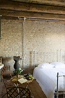 The rustic bedroom has exposed brick walls, bare beams and wrought-iron furniture