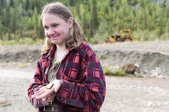 Girl with gold nugget at placer mine in the Klondike near Dawson City, Yukon