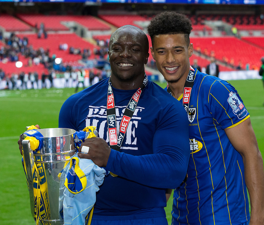 AFC Wimbledon's two goalscorers Lyle Taylor and Adebayo Akinfenwa pose with the winner's trophy<br /> <br /> Photographer Craig Mercer/CameraSport<br /> <br /> Football - The Football League Sky Bet League Two Play-Off Final - AFC Wimbledon v Plymouth Argyle - Monday 30 May 2016 - Wembley Stadium - London<br /> <br /> World Copyright &copy; 2016 CameraSport. All rights reserved. 43 Linden Ave. Countesthorpe. Leicester. England. LE8 5PG - Tel: +44 (0) 116 277 4147 - admin@camerasport.com - www.camerasport.com