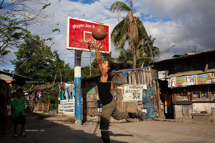 UK celebrity Myleene Klass (in black) plays a bit of basketball with the community after visiting underprivileged mothers in an urban slum in Paranaque City, Metro Manila, The Philippines on 19 January 2013. Photo by Suzanne Lee for Save the Children UK