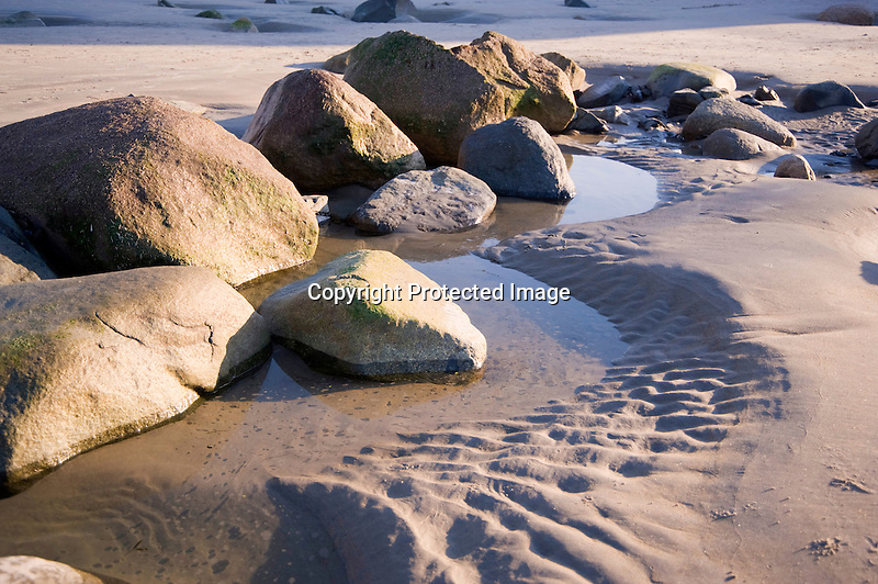 Rocks and Tidal Pools and Sand Patterns on a Sunny Maine Beach