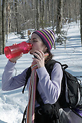 A adult female hiker wearing a scarf  takes a water break while hiking on Starr King Trail in the White Mountains, New Hampshire USA
