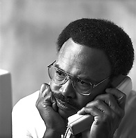 African-American male businessman wearing glasses, talking on phone while looking at his computer screen; professional; concentration; baffled, occupations, Black man, black and white image; 4x5 orig. Dave Johnson.