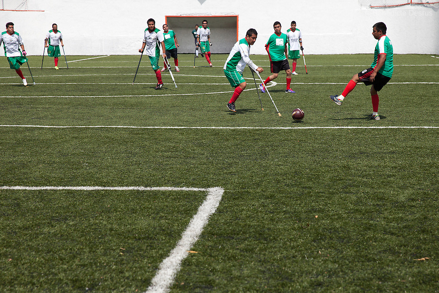 "Players from Guerreros Aztecas during a soccer game in Mexico City, Mexico on July 24, 2014. Guerreros Aztecas (""Aztec Warriors"") is Mexico City's first amputee football team. Founded in July 2013 by five volunteers, they now have 23 players, seven of them have made the national team's shortlist to represent Mexico at this year's Amputee Soccer World Cup in Sinaloa this December. The team trains twice a week for weekend games with other teams. No prostheses are used, so field players missing a lower extremity can only play using crutches. Those missing an upper extremity play as goalkeepers. The teams play six per side with unlimited substitutions. Each half lasts 25 minutes. The causes of the amputations range from accidents to medical interventions – none of which have stopped the Guerreros Aztecas from continuing to play. The players' age, backgrounds and professions cover the full sweep of Mexican society, and they are united by the will to keep their heads held high in a country where discrimination against the disabled remains widespread. (Photo by Bénédicte Desrus)"