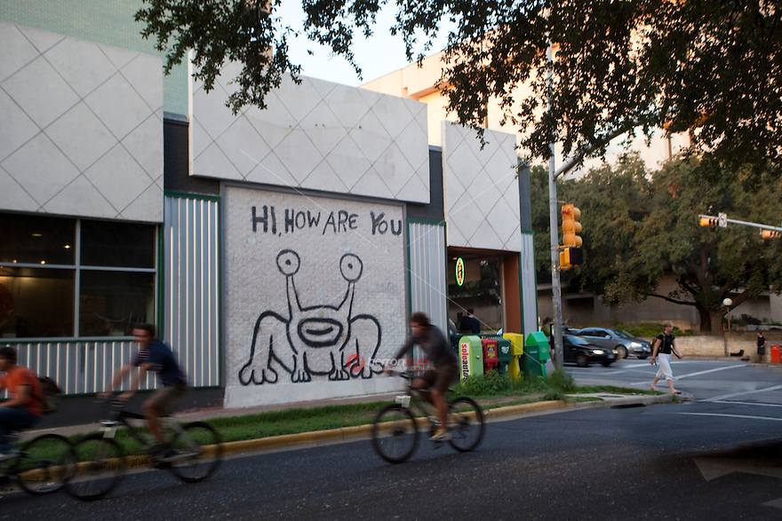 "Bike Riders ride past the famous ""Hi, How Are You"" Mural, a famous tourist attraction on the UT Drag"