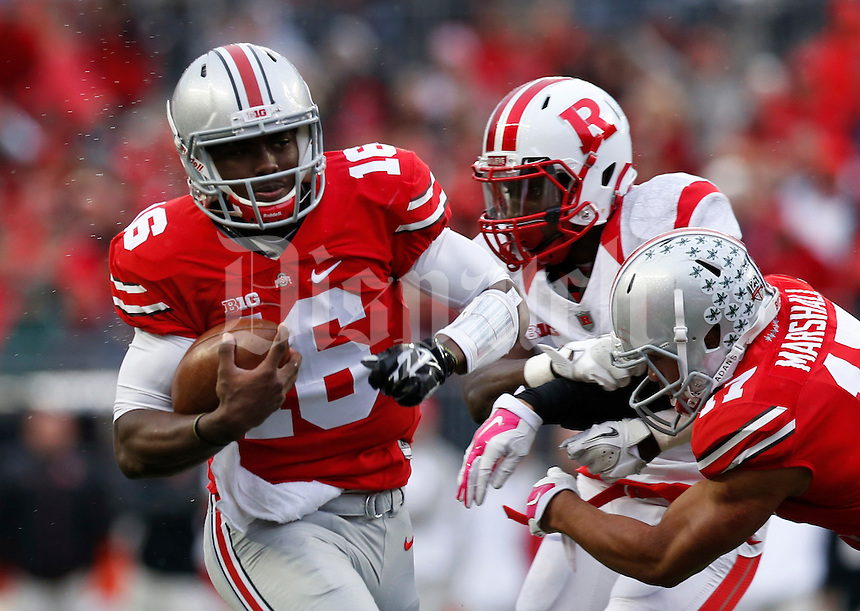 Ohio State Buckeyes quarterback J.T. Barrett (16) gets a block from teammate running back Jalin Marshall (17) on his way to to scoring a rushing touchdown during the third quarter of the NCAA football game at Ohio Stadium in Columbus on Oct. 18, 2014. (Adam Cairns / The Columbus Dispatch)