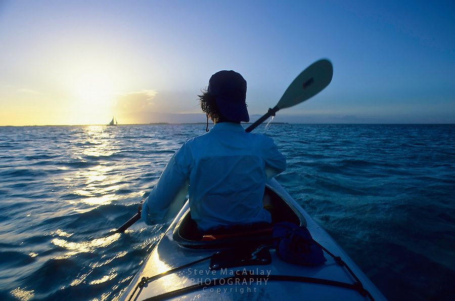 Female paddler in front cockpit  of double kayak paddling ofshore from Tobacco caye, Belize