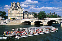 Tour boat on Seine River in front of the Louvre, Paris, France.